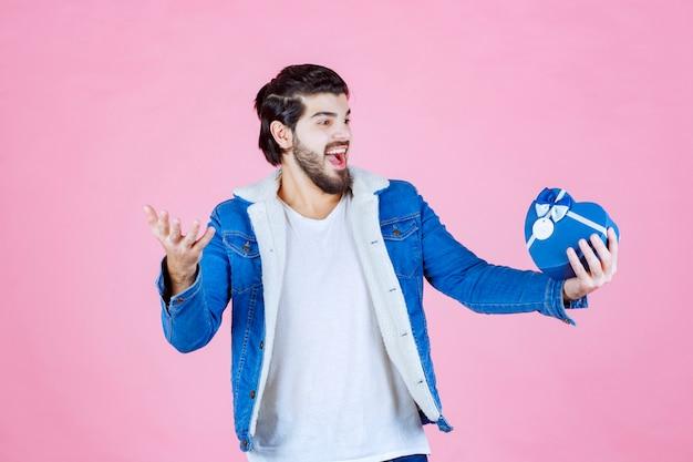 青いハート型のギフトボックスを持って幸せそうに見える男