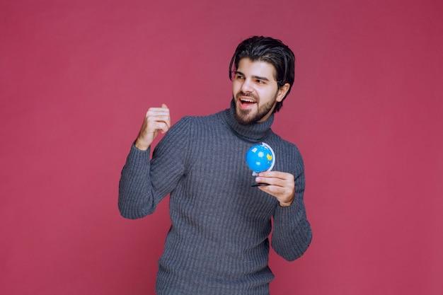 Мужчина держит голубой мини-глобус и демонстрирует его толпе.