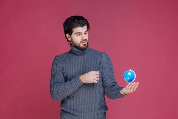 파란색 미니 지구본을 들고주의 깊게 보는 남자.