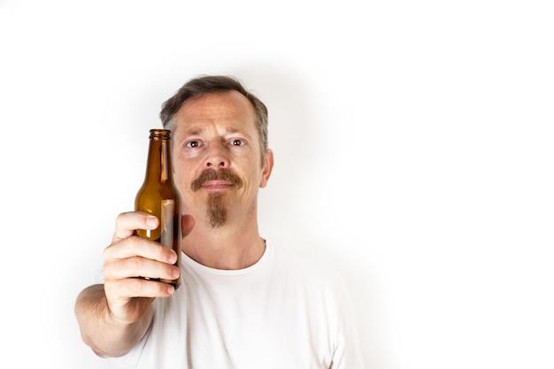 Мужчина держит бутылку пива перед его ртом на белом