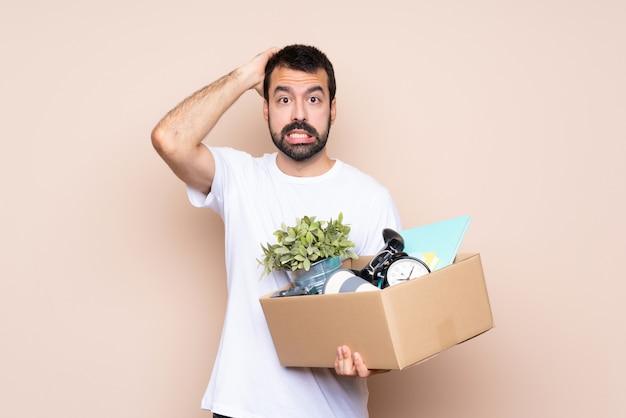 남자는 상자를 들고 격리 된 배경 위에 새 집으로 이동 좌절과 머리에 손을