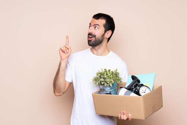 Человек, держащий коробку и переезда в новый дом, думая, идея, указывая пальцем вверх