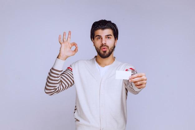 비즈니스 카드를 들고 좋은 손 기호를 만드는 남자.