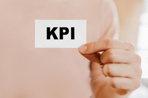 Мужчина держит визитную карточку с kpi