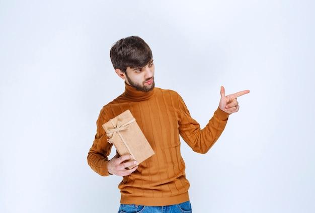 Мужчина держит картонную подарочную коробку и звонит кому-то справа.