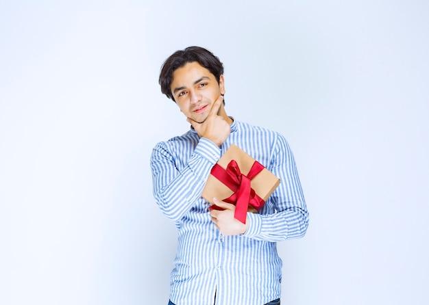 Мужчина держит картонную подарочную коробку с красной лентой и колеблется или смущен. фото высокого качества