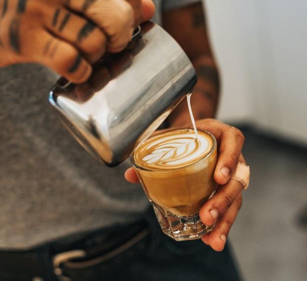 Мужчина держит прозрачный стакан с кофе и наливает молоко