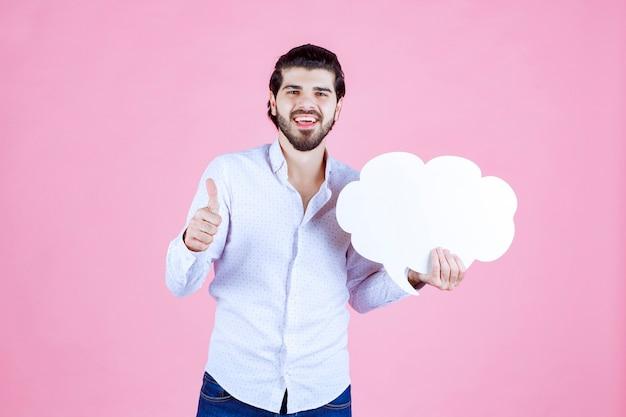 Мужчина держит ideaboard форму облака и наслаждается этим.