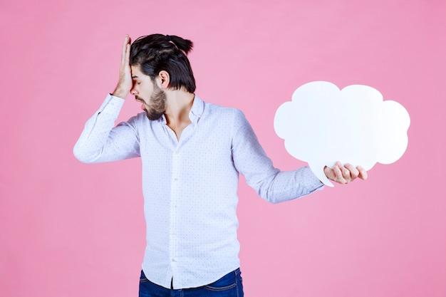 雲の形の思考板を持って不満そうな男。