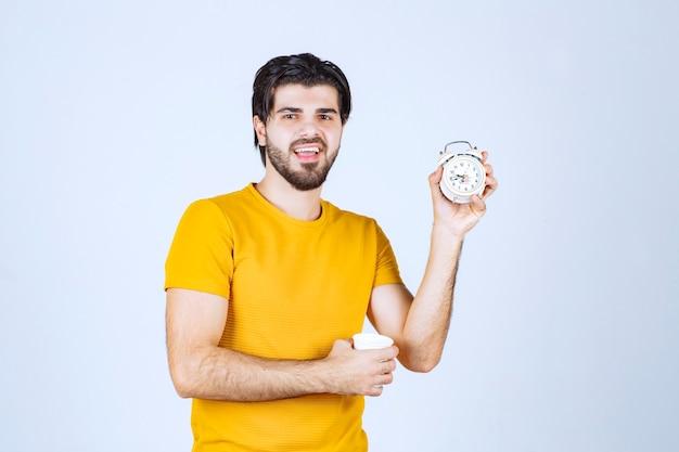 朝のルーチンを指しているコーヒーカップと目覚まし時計を持っている男。
