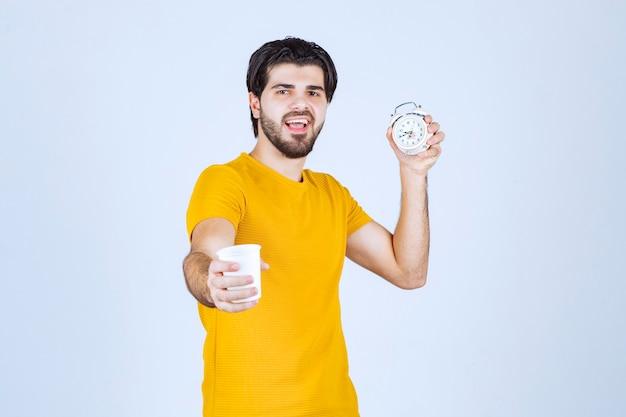 커피 컵과 아침 루틴을 가리키는 알람 시계를 들고 남자.
