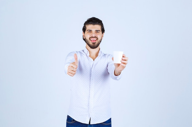 커피 컵을 들고 맛을 즐기는 남자