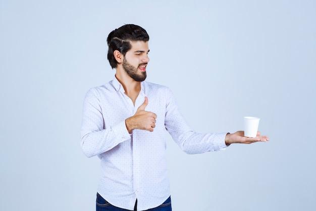 Мужчина держит чашку кофе и наслаждался вкусом