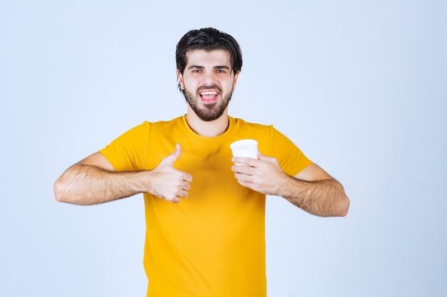 コーヒーカップを持って味を楽しんでいる男。