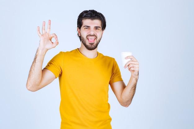 커피 컵을 들고 맛을 즐기는 남자.