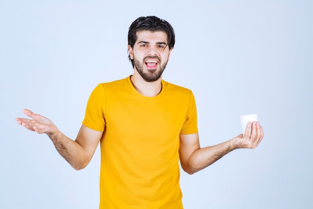 커피 컵을 들고 손바닥을 사용하여 프레젠테이션을 남자.