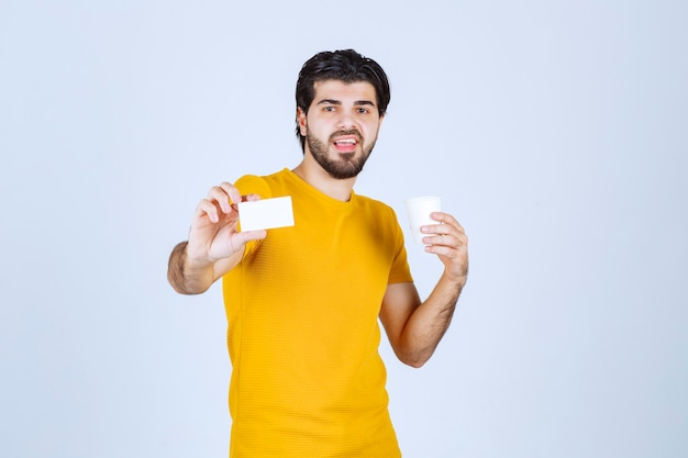 コーヒーカップを持って名刺を提示する男。