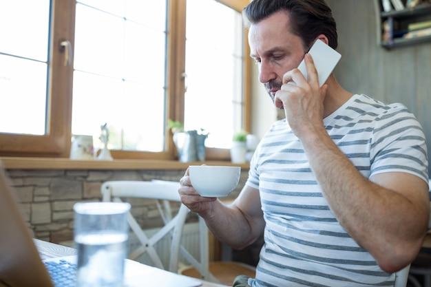 男のコーヒーカップを保持し、携帯電話で話します