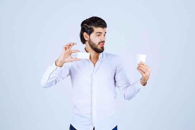 片手にコーヒーカップを持ち、もう片方の手に名刺を提示する男