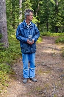森の中で野生のブルーベリーの入った容器を持っている男。十分に収集されていません。
