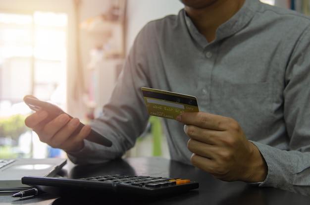 신용 카드와 휴대 전화를 들고 온라인으로 상품이나 서비스 비용을 지불하거나 온라인 쇼핑을 하는 남자. 개념 금융 사업