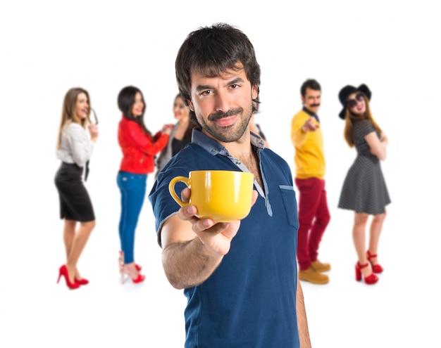 白い背景の上にコーヒーのカップを持っている男