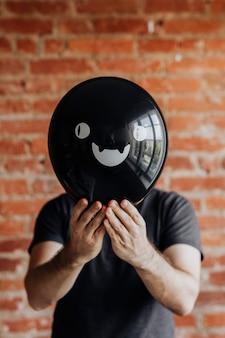 Мужчина держит милый черный воздушный шар хэллоуина
