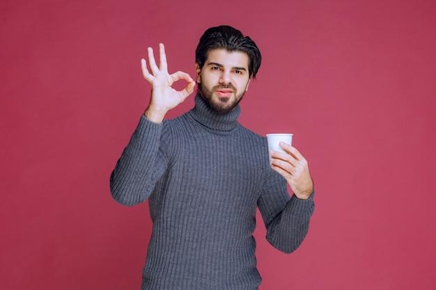 使い捨てのコーヒーカップを持って、楽しみのサインを作る男。