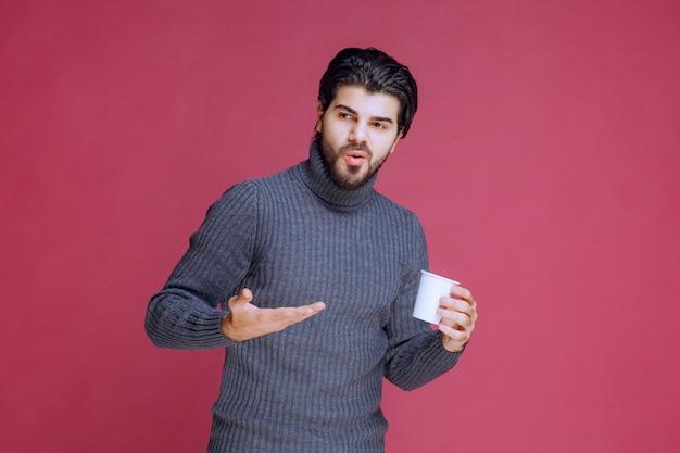 使い捨てのコーヒーカップを持ってそれを指さしている男。