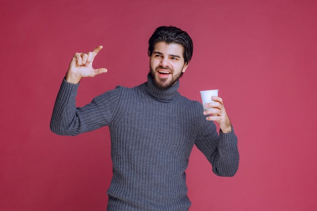 使い捨てのコーヒーカップを持って、彼がどれだけ必要かを示している男。