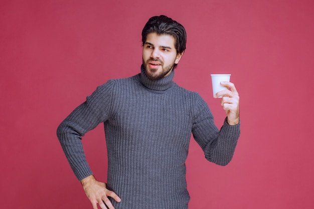 일회용 커피 컵을 손에 들고 긍정적 인 느낌을주는 남자.