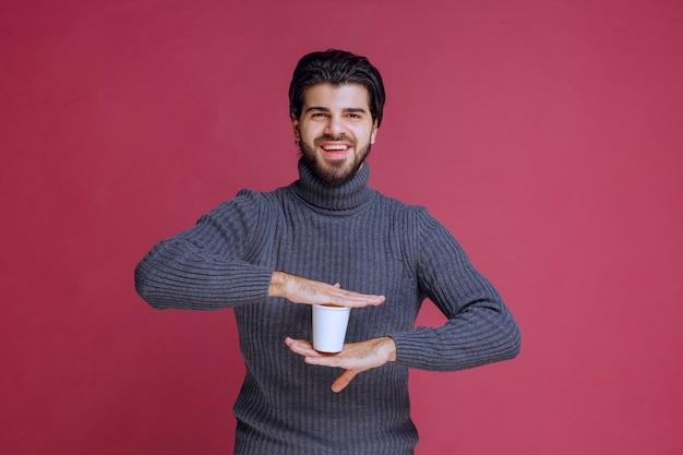 使い捨てのコーヒーカップを手に持って前向きに感じる男。