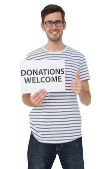 親指を握っている間、寄付のウェルカムノートを持っている男