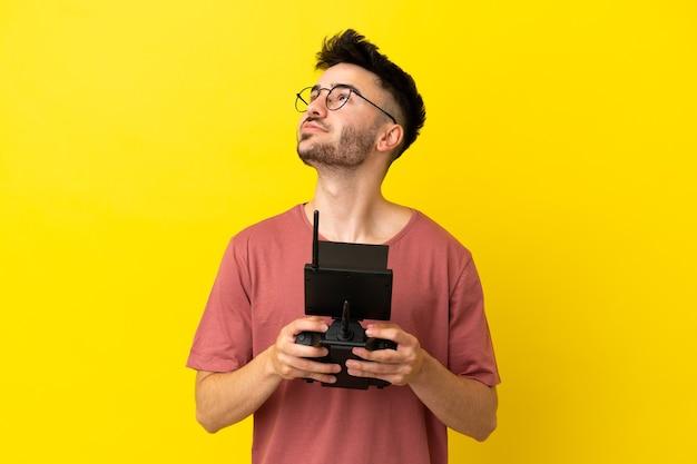 黄色の背景で隔離のドローンのリモコンを保持し、見上げる男