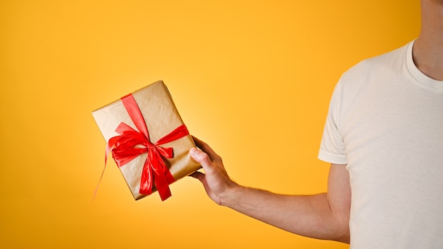 Мужчина держит подарок крупным планом на желтом