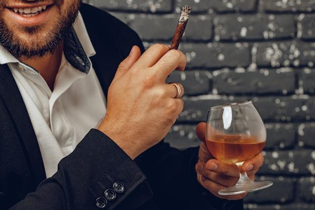 ウイスキーと火のついたタバコのグラスを手に持っている男クローズアップ写真