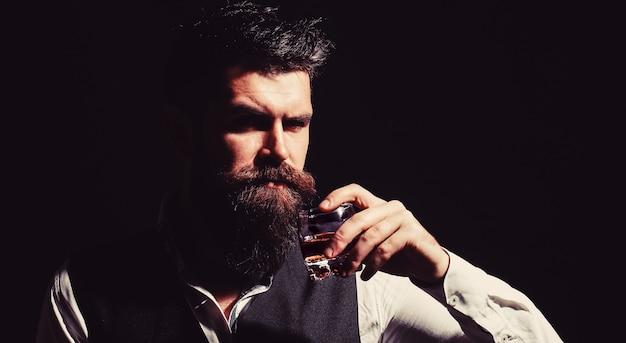 ウイスキーのグラスを持っている男。ウイスキーをすすりながら。厚いひげを持つ男の肖像画。マッチョな飲酒。デグステーション、テイスティング。あごひげを生やした男はガラスのブランデーを保持しています。ひげを生やした飲み物のコニャック。ソムリエは飲み物を味わいます。