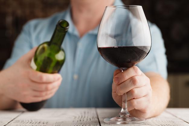 Мужчина держит бокал с красным вином и бутылкой
