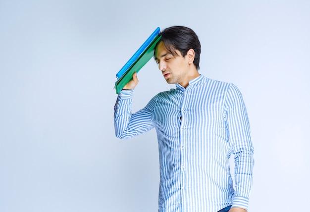 녹색 보고서 폴더를 잡고 생각하는 남자. 고품질 사진
