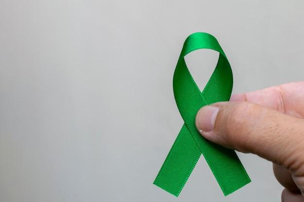 녹색 리본을 들고 남자입니다. 간, 담낭, 신장 및 림프종 암 인식의 달 개념.