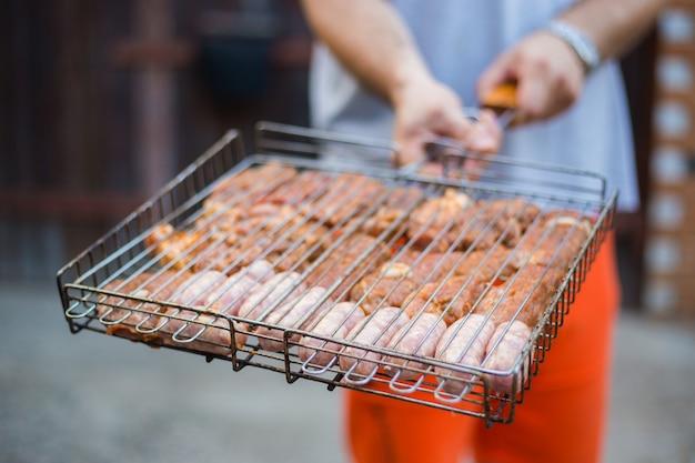 肉とグリルを持っている男。外の国で休んでください。バーベキューグリル屋台の食べ物。夏のバーベキュー料理、面白いピクニック。