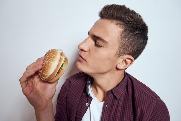 手にハンバーガーを持っている男