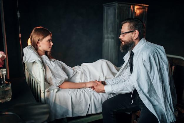 ベッドで病気の愛する女性の手を握って男