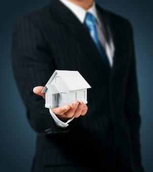 Мужчина держит в руке дом