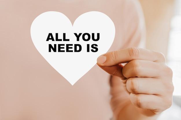 Мужчина держит любовную карту в форме сердца со всем, что вам нужно, это любовь