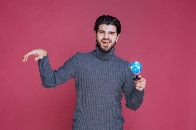Мужчина держит мини-глобус и отправляет приветствия.