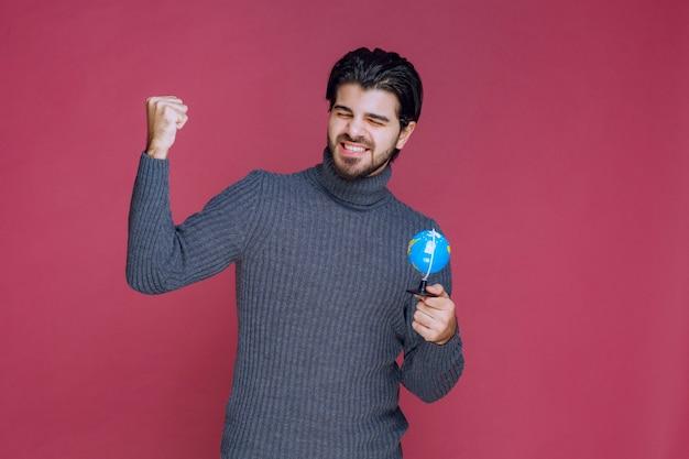 Мужчина держит мини-глобус и показывает кулак.