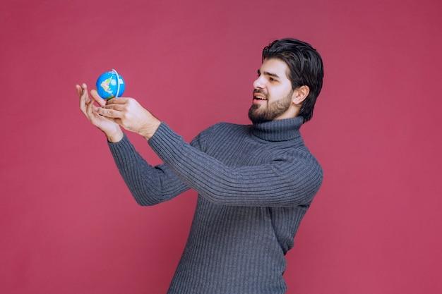 Мужчина держит мини-глобус и пытается найти там место.