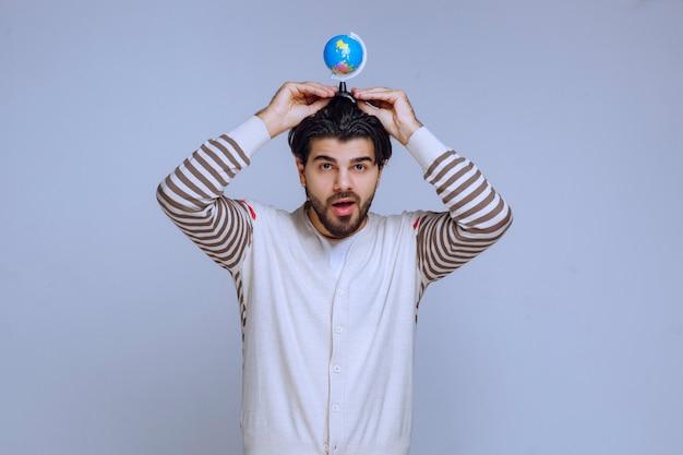 그의 머리 위에 미니 지구본을 들고 남자입니다.