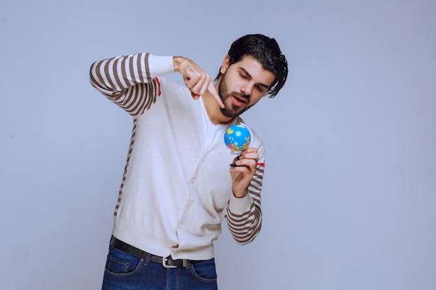 Мужчина держит мини-глобус, трясет им и пытается угадать местоположение.